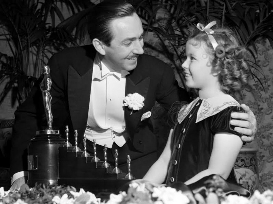 Shirley-Temple-with-Walt-Disney-after-presenting-him-with-his-Honorary-Academy-Award-for-Snow-White-and-the-Seven-Dwarfs-at-the-11th-Academy-Awards-Ceremony-on-Feb-23-1939.